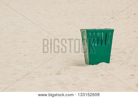 Empty old green trash can on sand at the beach concept of environmental protection littering of environmental copy space for text