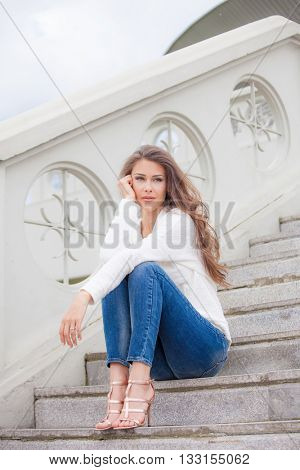 young woman sit on stairs in the city full body shot
