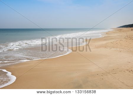 Isolated sandy beach in wintertime with calm sea and blue sky