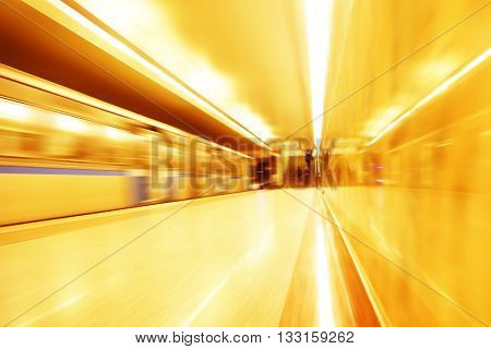 Subway train in motion blur and blurred people on background.