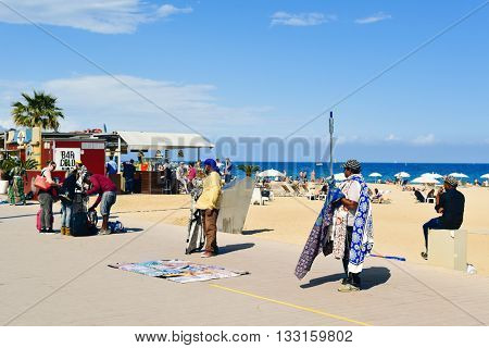 BARCELONA, SPAIN - MAY 30: Some street hawkers selling different objects at the seafront of La Barceloneta Beach on May 30, 2016 in Barcelona, Spain. This is the main beach of the city