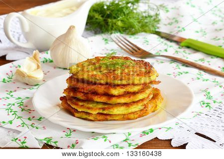 Pancake made from zucchini, eggs, flour, salt, garlic, dill. Delicious zucchini fritters on a plate. Fork, knife, green dill, gravy boat, garlic, napkin. Easy and healthy zucchini recipe.