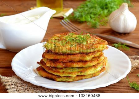 Squash delicious fried pancake with dill. Fried golden pancakes with zucchini and dill. Make delicious zucchini dishes. Cheap and easy meal idea. Sauce, garlic, fork, olive oil, dill on a wooden table