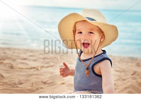 one year old boy sitting at the beach in straw hat