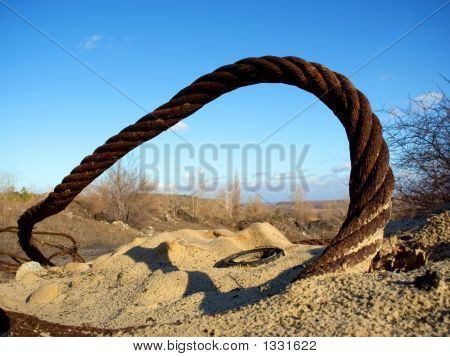 Thick Rusty Wire Rope And Ring In Sand