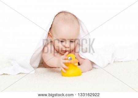 Sweet small baby covered with a towel, lies on a plaid on a white background.Cute infant after bath. 5 months old.
