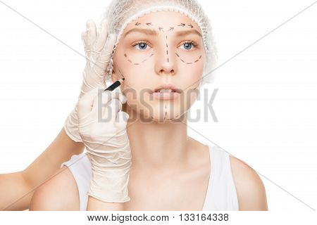 Portrait of young woman with plastic surgery outlines on face