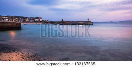 Long exposure sunrise St. Ives harboour Cornwall England shoreside lamps still illuminated as the day breaks