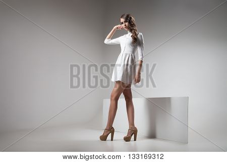 Young model with hairstyle in white dress posing in studio.