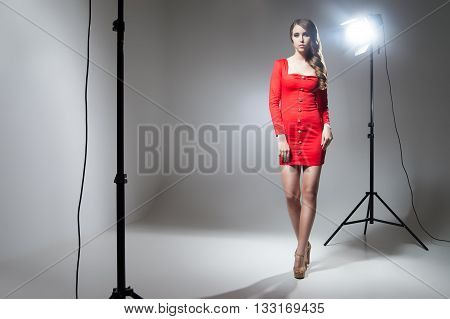 Seductive model in red dress in spotlight.Studio shot