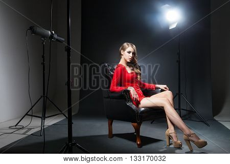 Portrait of beautiful young model in red dress on leather chair in spotlight
