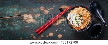 Asian noodles with vegetables and mushrooms soy sauce sticks on a dark background top view with copy space