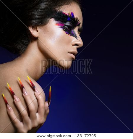 Beautiful girl in the image of the Phoenix bird with creative makeup and long nails. Manicure design. The beauty of the face. Photos shot in studio