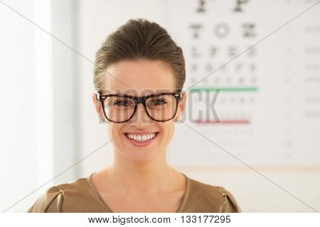 Smiling Young Woman Wearing Eyeglasses In Front Of Snellen Chart