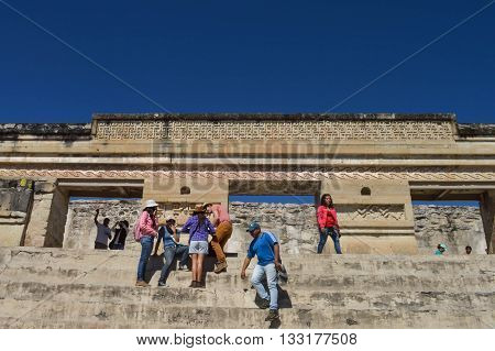 Oaxaca Mexico - November 15 2014: Tourists are seen visiting and posing for photos in front of the main pyramid at the archaeological site of Mitla in the state of Oaxaca Mexico