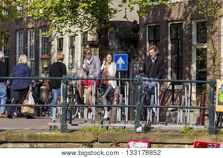 AMSTERDAM, NETHERLANDS - MAY 5, 2013: Biking does not distract the residents of Amsterdam from food or from a mobile phone.