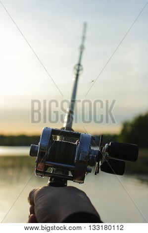 Male hand holding a round fishing reel attached to a fishing rod with blurred sea nature on the background at sunset time.