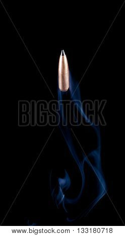 Copper plated bullet with a polymer tip headed up with smoke behind