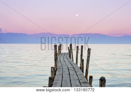 Little wooden boat dock with the pink sunset sky on the background in Lake Atitlan, Guatemala