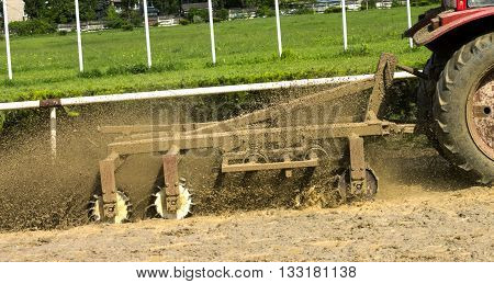 Tractor plowing race course track at Hippodrome in the Circle Nalchik Caucasus Russia.