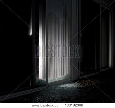 House with a shattered sliding glass door and flashlight on inside