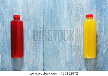 Healthy eating. Smoothie vegan drinks flat lay, top view at blue rustic wood background. Berry and orange healthy, dieting energetic fruit drinks in bottles with copyspace. Smoothie in bottles.