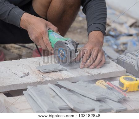 Worker Cutting A Sand Stone Tile Using An Angle Grinder