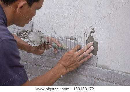 NAKHON RATCHASIMA -MAY 31: worker install stone wall tile with cement for house decoration on May 31 2016 in Nakhon Ratchasima Thailand