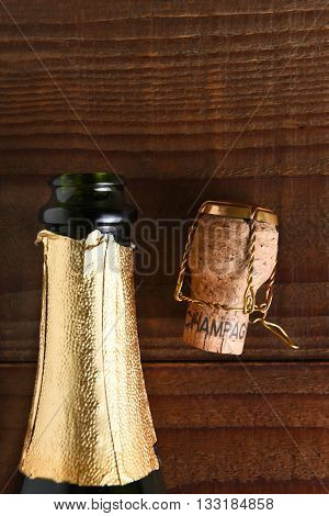 Top view of an opened Champagne bottle next to a cork and cage. Vertical format on dark wood background, with copy space.