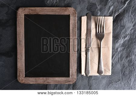 High angle view of a blank chalkboard menu next to silverware on a napkin. Strong side light on a slate table.