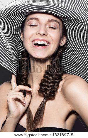 Beautiful cheerful girl in a summer beach striped hat. The beauty of the face. Photos shot in the studio.