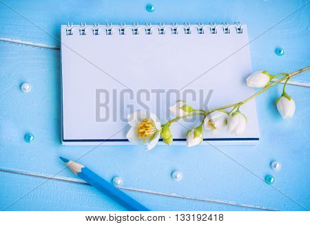 Blank notepad, blue pencil, beads and jasmine flowers on painted wooden background