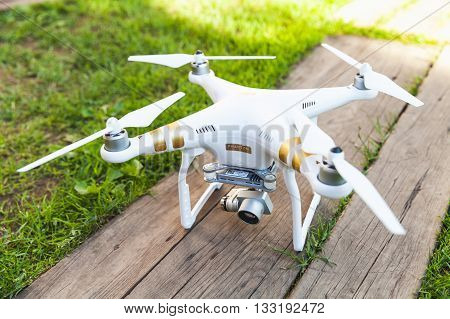 St. Petersburg Russia - May 4 2016: Drone quadrocopter Phantom 3 Professional with high resolution digital camera designed by the Chinese company DJI stands on a wooden floor in garden
