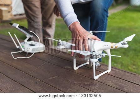 St. Petersburg Russia - May 4 2016: Drone quadrocopter Phantom 3 Professional with high resolution camera designed by the Chinese company DJI stands on a wooden floor blurred pilot on a background
