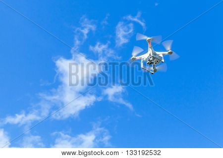 St. Petersburg Russia - May 4 2016: Drone quadrocopter Phantom 3 Professional with high resolution digital camera designed by the Chinese company DJI soars in blue cloudy sky