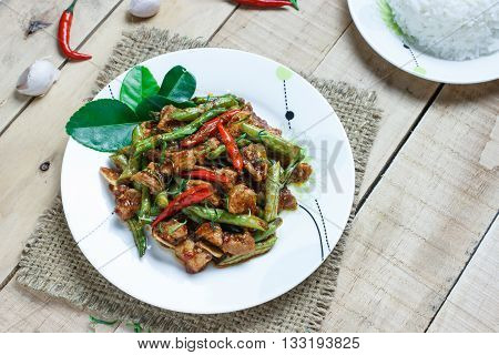 Stir fried pork and red curry paste with string bean on wood background
