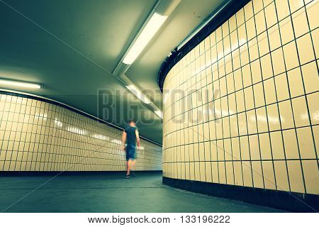 Pedestrian is walking in underground passage from subway. Alone young man is going to the city.