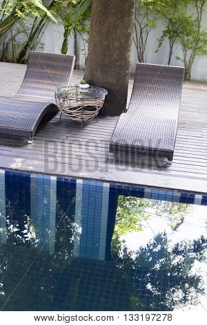 brown rattan wicker sunbed beside swimming pool