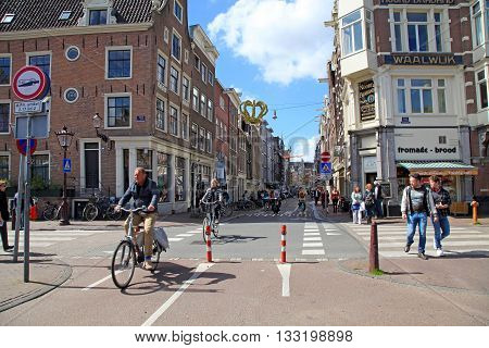 AMSTERDAM, NETHERLANDS - MAY 3, 2016: Local people on bicycle in historical center in Amsterdam, the Netherlands. Bicycles outnumber people in Amsterdam: 760000 citizens and nearly a million bikes.