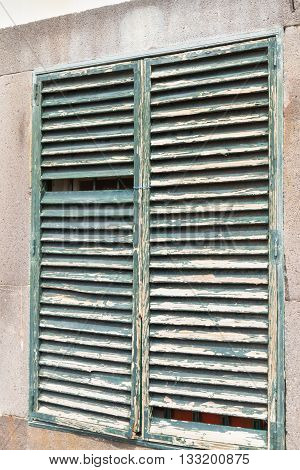 Close up of wethered green shutter on old building