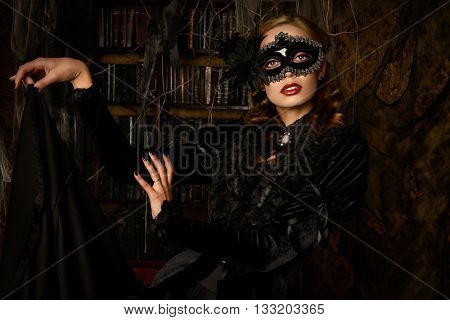 Charming mysterious girl in black mask and black medieval dress stands in a castle living room. Vampire. Halloween concept. Vintage style.