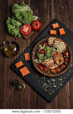 Grilled cut beef stake entrecote with vegetables, bread and species on the wooden desk background.