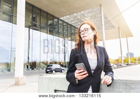 Young businesswoman holding her smart phone and looking away from camera. The building on background is the Paul-Lobe house in Berlin. The woman looks focused and resolute.