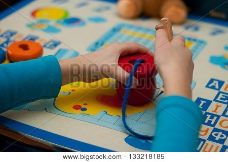 child collects logical toy on a lace