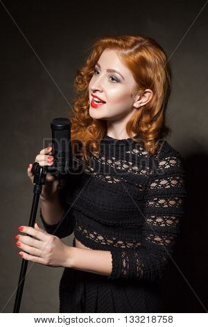 Close-up of red-haired woman signing song in mic.Studio shot