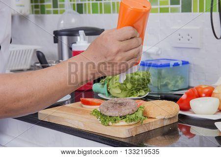 Chef putting mayonnaise on the Hamburger bun /Cooking Hamburger concept