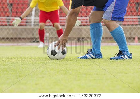 Soccer player preparing foot ball for a penalty shot