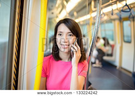 Woman talk to phone inside train compartment
