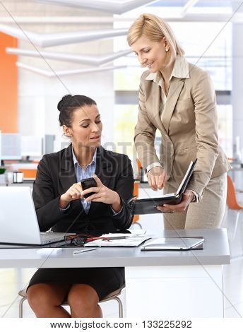 Mid-adult caucasian brunette businesswoman with secretary at business office desk, checking mobile phone and personal organizer for schedule.