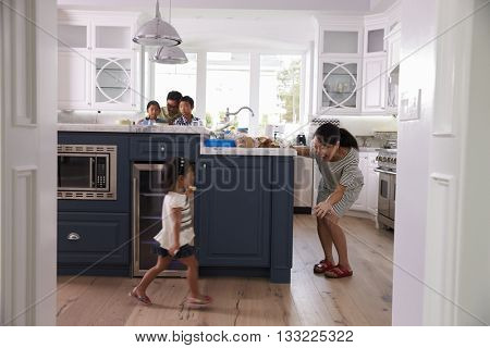 Parents Prepare Food As Children Play In Kitchen